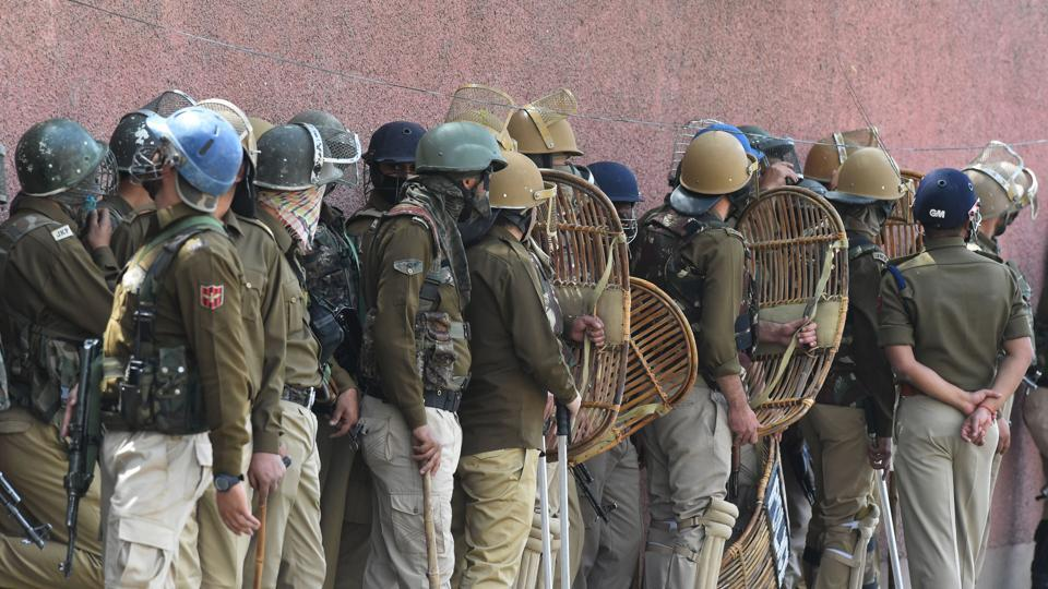 Police stand guard during clashes outside a college in Srinagar.