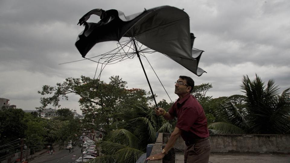 A man's umbrella gives way under strong wind blowing in Guwahati, Assam, on May 15, 2018. (Anupam Nath / AP)