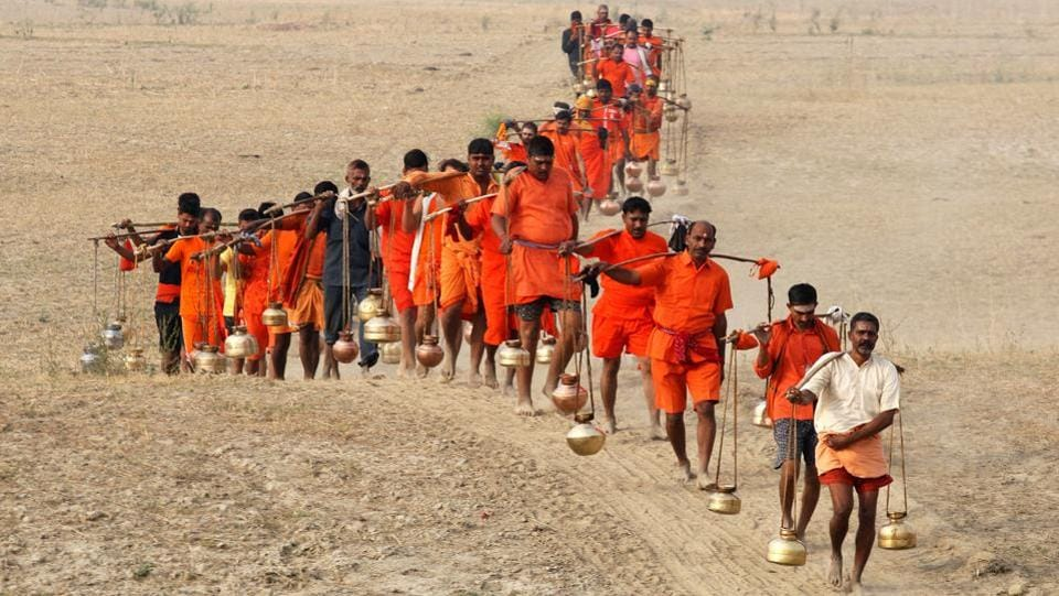 Kanwariyas carry metal pots filled with holy water after taking a dip in the waters of the river Ganga, to offer it to Lord Shiva for the betterment of their families and society, in Allahabad, Uttar Pradesh, on May 16, 2018. (Jitendra Prakash / REUTERS)