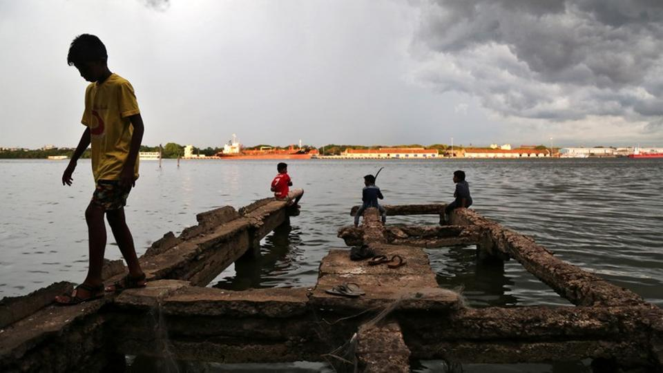 A boy walks through a damaged jetty as pre-monsoon clouds gather above the Vembanad Lake in Kochi, Kerala on May 11, 2018. (Sivaram V / REUTERS)