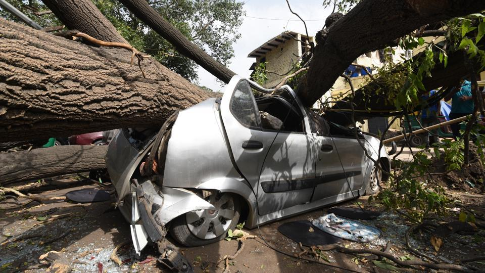 A huge tree fell over a car due to sudden late midnight dust storm that hit New Delhi, on  May 16, 2018. (Arvind Yadav / HT Photo)