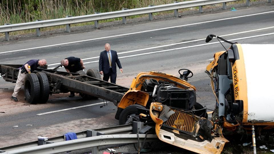 Police investigators look at the wreckage of a school bus on Interstate 80 following an accident with a dump truck in Mount Olive Township, New Jersey, US.