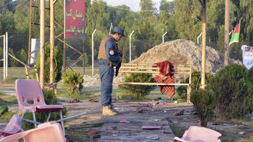 A policeman inspects the site of a bomb attack at a cricket stadium in Jalalabad city, capital of eastern Nangarhar province, Afghanistan, Saturday, May 19, 2018.