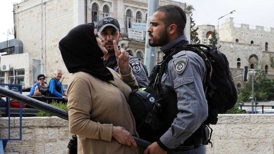 An Israeli police officer argues with a Palestinian woman outside Jerusalem's Old City's Damascus Gate. (Ammar Awad / REUTERS)