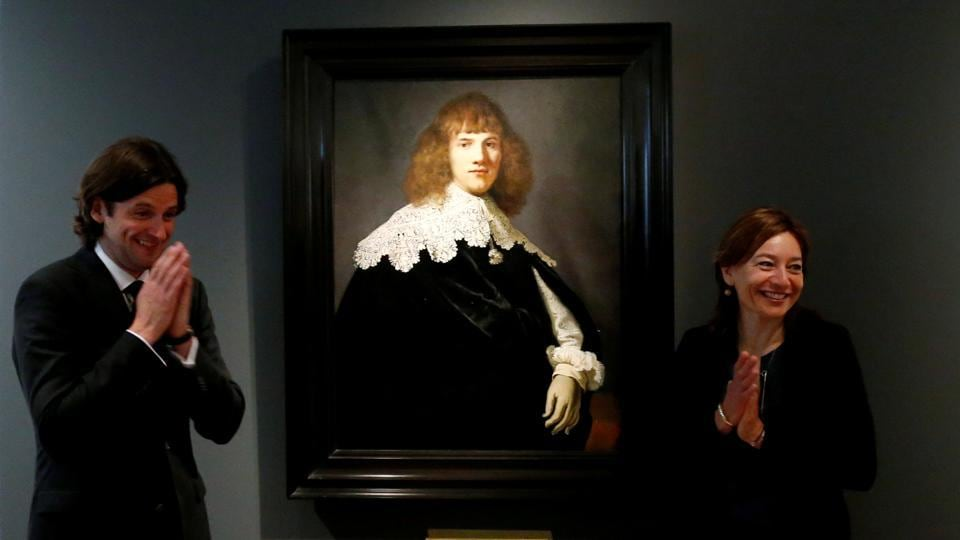 Dutch art dealer Jan Six and Museum Director Cathelijne Broers react as they stand next to a Rembrandt painting called 'Portrait of a Young Man' at Hermitage Amsterdam, Netherlands. Portrait of a Young Gentleman is the first new Rembrandt to come to light in 44 years. (Francois Lenoir / REUTERS)