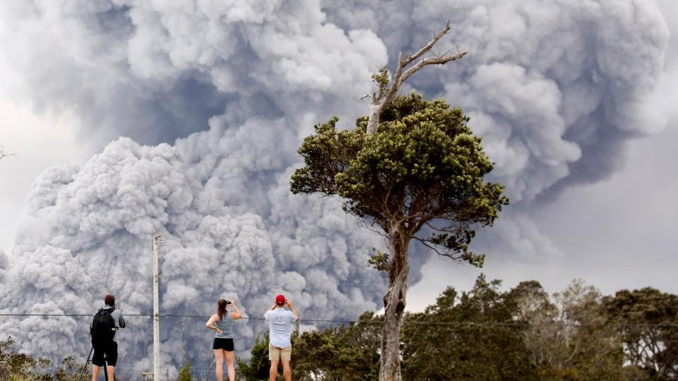 People watch as ash erupts from the Halemaumau crater near the community of Volcano during ongoing eruptions of the Kilauea Volcano in Hawaii. (Terray Sylvester / REUTERS)