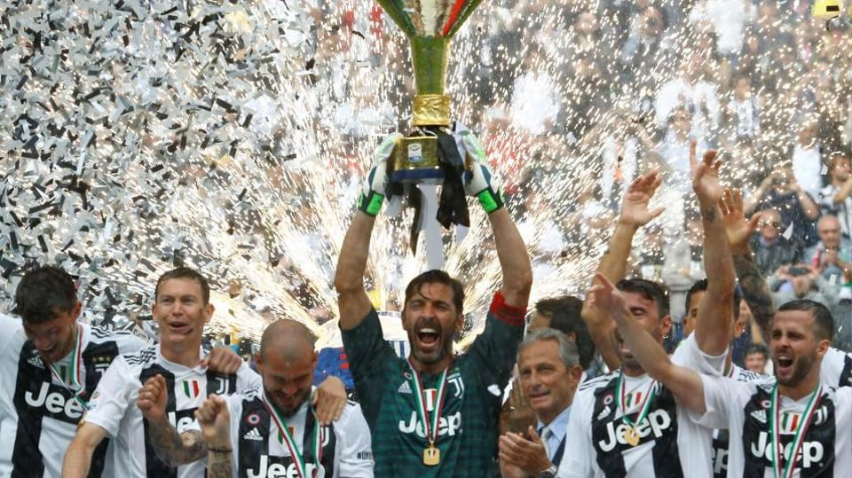 Gianluigi Buffon lifts the Serie A trophy as Juventus players celebrate winning the league at the Allianz Stadium in Turin on Saturday.