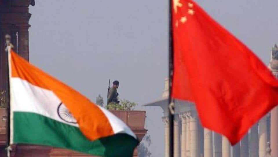 An Indian paramilitary officer is framed by an Indian (L) and Chinese (R) flags as he stands guard near the presidential palace in New Delhi, 12 January 2002.
