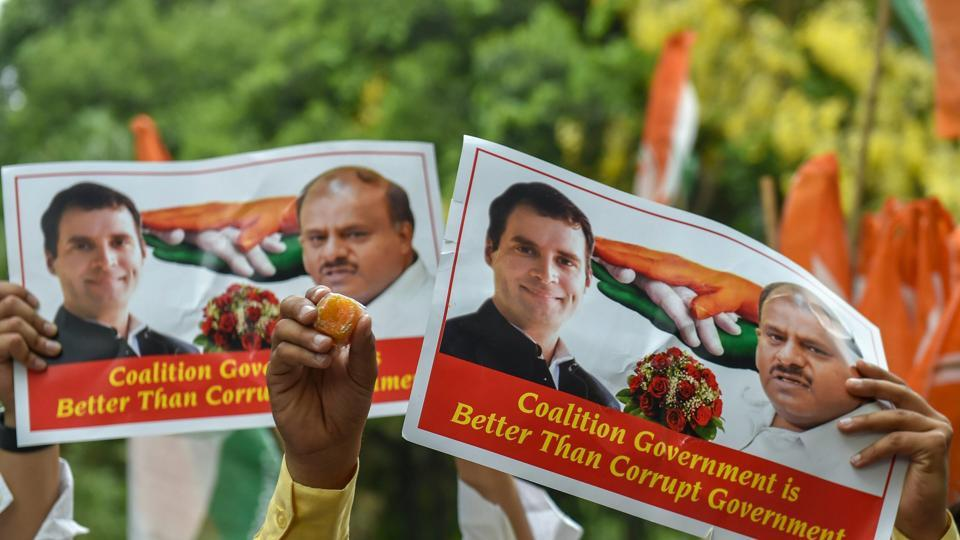 Congress supporters raise posters of party president Rahul Gandhi and JD chief HD Kumarswamy after Karnataka Chief Minister BS Yeddyurappa announced his resignation in New Delhi May 19