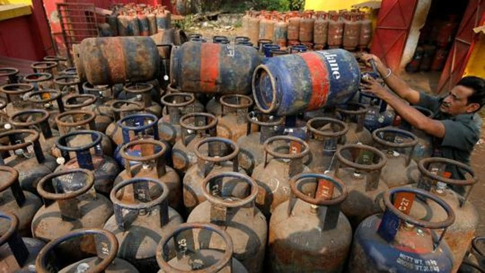 A worker arranges empty cooking gas cylinders at a depot in Kolkata. Since the LPG stove is about as costly as the connection, and the fuel several times costlier per year, almost two-thirds of all households given a connection will continue to use or soon revert to mostly using polluting wood.