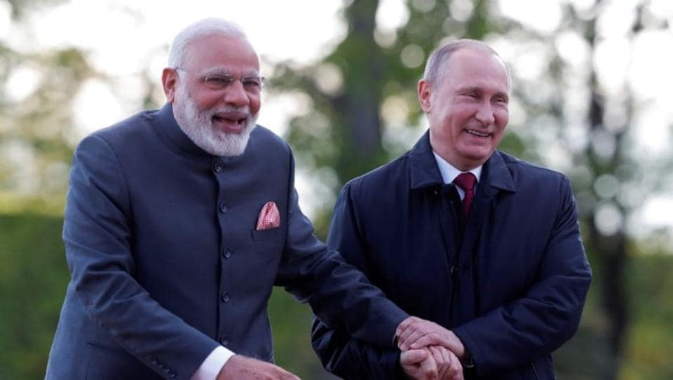 Russian President Vladimir Putin (R) and Indian Prime Minister Narendra Modi react while walking near the Constantine (Konstantinovsky) Palace during their meeting in St. Petersburg, Russia, on June 1, 2017.