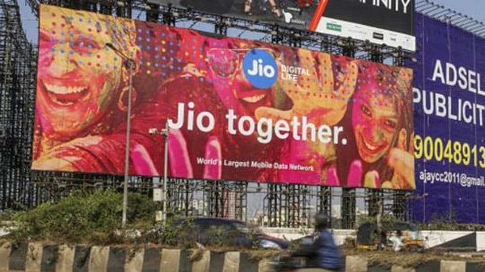 Traffic travels past a billboard for Reliance Jio Infocomm Ltd. in the Bandra area of Mumbai, India.