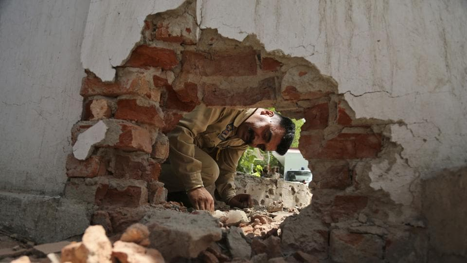 A policeman looks at a hole made in a wall of a police station caused as Pakistani Rangers opened fire and lobbed mortars along the International Border in Jammu and Kashmir early on Tuesday. This triggered panic among border residents and forced many to take shelter in government-run camps. Two persons were injured. (Channi Anand / AP)