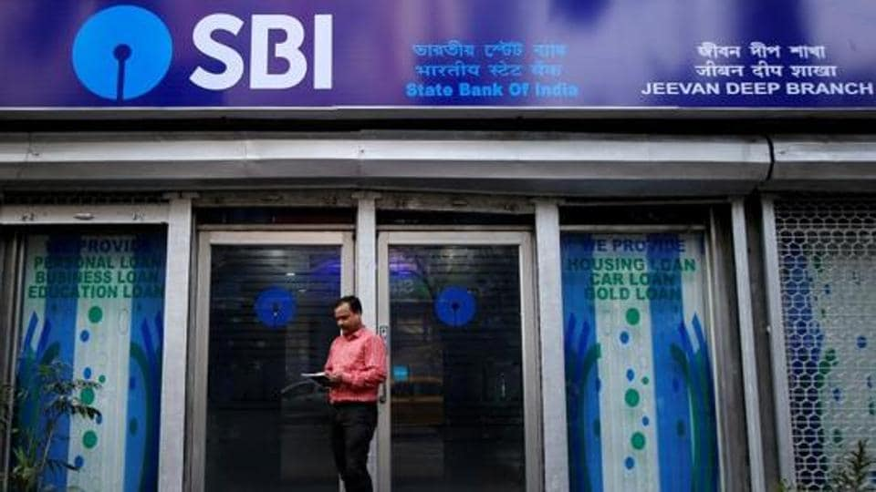 A man checks his mobile phones in front of State Bank of India (SBI) branch in Kolkata, India.