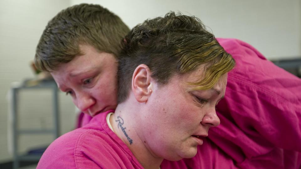 "Mary Sammons, 41, foreground, is comforted by cellmate Blanche Ball, 30, days after Sammons learned that her 20-year-old son was murdered in Kentucky. Sammons, who was arrested on drug-related charges, suspects her son's murder was drug-related. ""I always pictured my kids burying me, not me having to bury my children. Young kids are losing their life over bad dope."" (David Goldman / AP)"