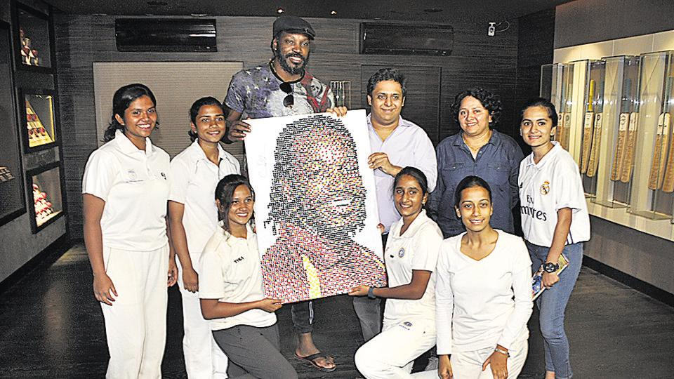 Chris Gayle with Pune's women cricketers at the Blades of Glory museum at Sahakarnagar in Pune on Tuesday.