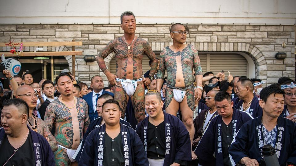 Japanese men sporting irezumi tattoos, associated with a life in the Yakuza, wait for the arrival of a mikoshi (portable shrine) near Asakusa Temple on the third and final day of Sanja Festival in Tokyo, Japan. Sanja Matsuri is one of Japan's major festivals and held annually in the Asakusa area of Tokyo. (Carl Court / Getty Images)