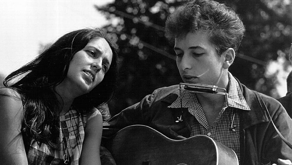 Singers Joan Baez and Bob Dylan during a civil rights rally on August 28, 1963 in Washington D.C. 'Folk music' in the 1960s is perhaps personified by Joan Baez and Bob Dylan and their live duets. When a young Dylan, aged 19, arrived in Greenwich in 1961, Baez had long been crowned the 'Queen of Folk'. By 1963, Dylan would join her at the top.  (Rowland Scherman / National Archive / Newsmakers / Getty Images)