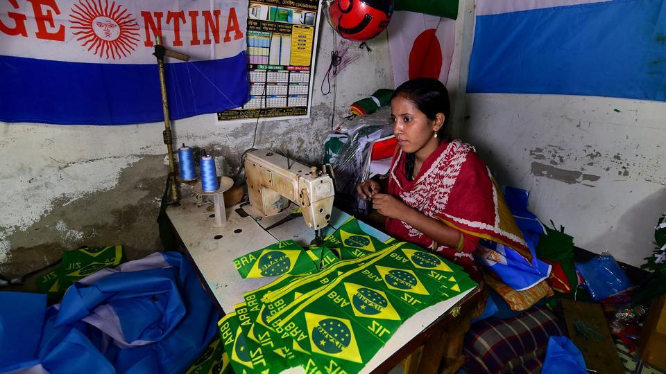 This photograph taken on May 17, 2018 shows a Bangladeshi worker sewing flags for FIFA World Cup football playing nations in Narayanganj, on the outskirts of Dhaka, ahead of Russia 2018.