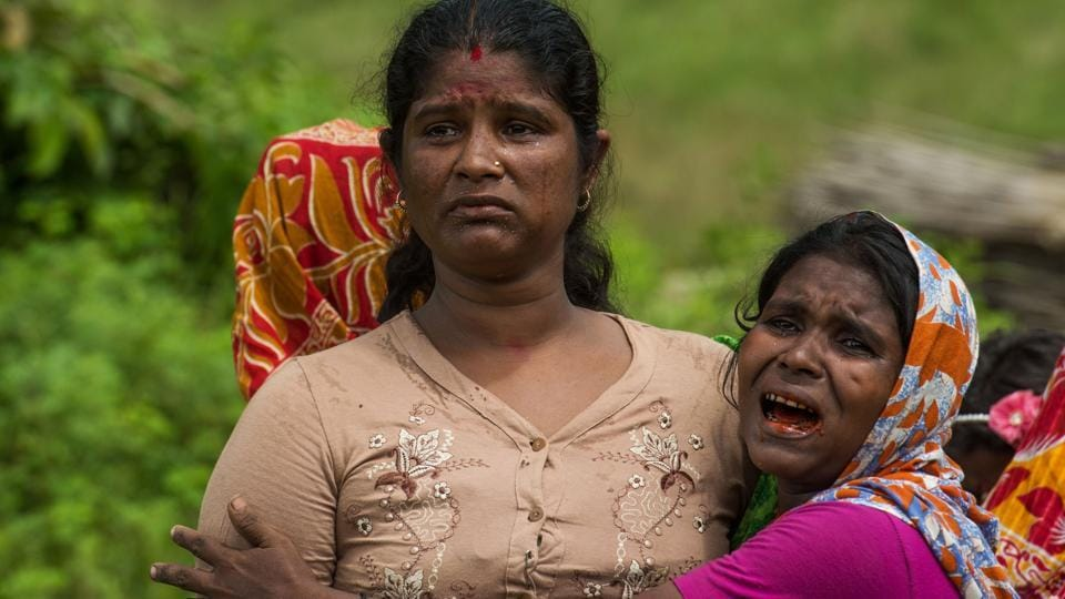 In this file photo taken on September 27, 2017, Hindu women cry near the dead bodies of their family members in Ye Baw Kyaw village, Maungdaw in Myanmar's northern Rakhine state.