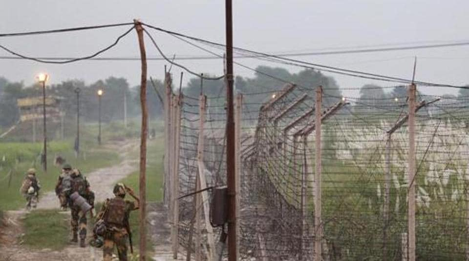 Indian Border Security Force soldiers walk with their belongings for night duty near the India-Pakistan international border area at Gakhrial boder post in Akhnoor sector.