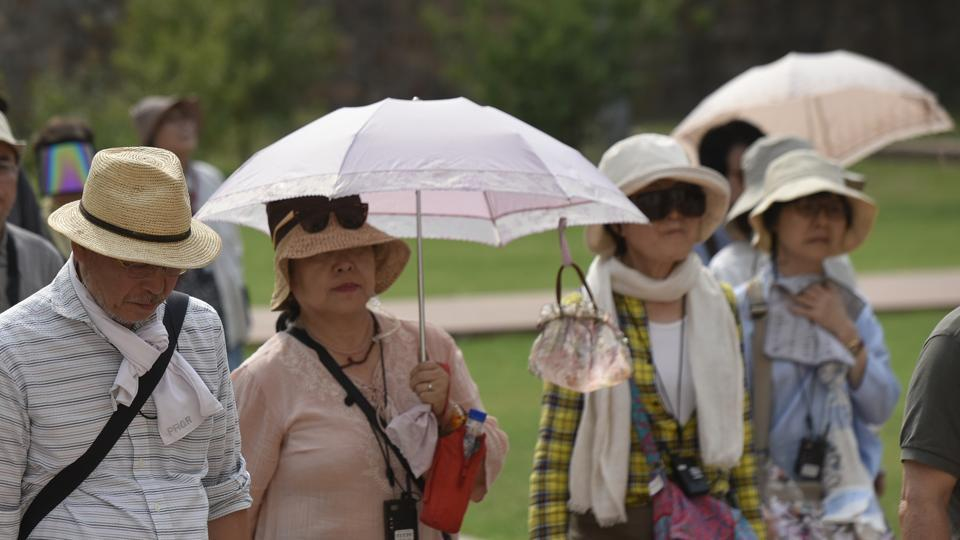 Tourists walk under umbrellas to protect themselves from scorching heat as they visit Humayun's Tomb, in New Delhi, on Tuesday.