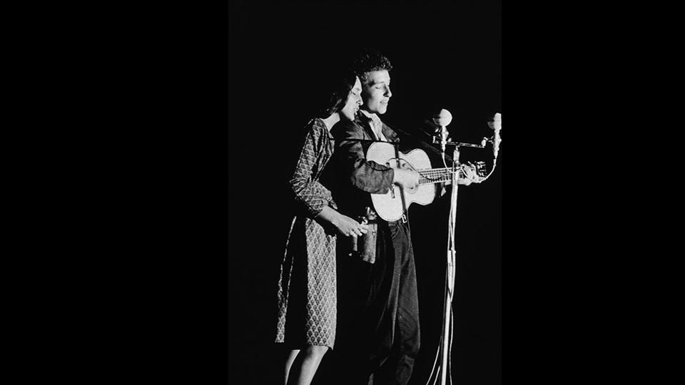 Joan Baez and Bob Dylan perform onstage, 1963. A relatively unknown Bob Dylan debuted at the 1963 Newport Festival performing two duets with Baez, one on her and another on his own set. Joining Baez's August tour later, introduced Dylan to the large audiences her fame pulled, playing a large role in his early rise to success. The next two years saw tables turning between them. (Columbia Records / Getty Images)