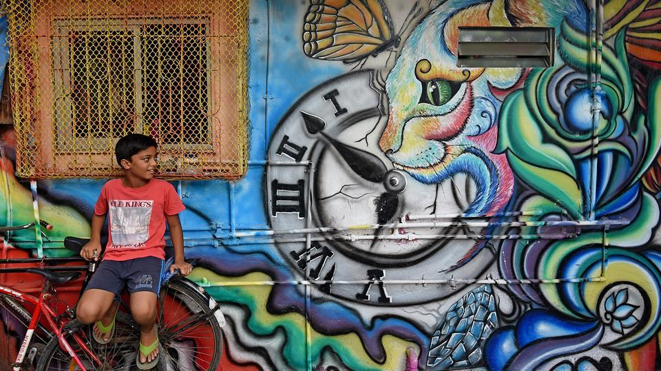 A boy sits on a bicycle next to a newly painted house in a slum at Khar Danda in Mumbai. Houses and shops in the slum colony were painted in the second week of May. (Satyabrata Tripathy/HT Photo)