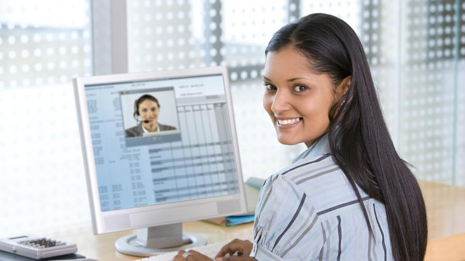Young businesswoman, smiles back over her shoulder while on an internet video chat with a businessman. Horizontal shot.