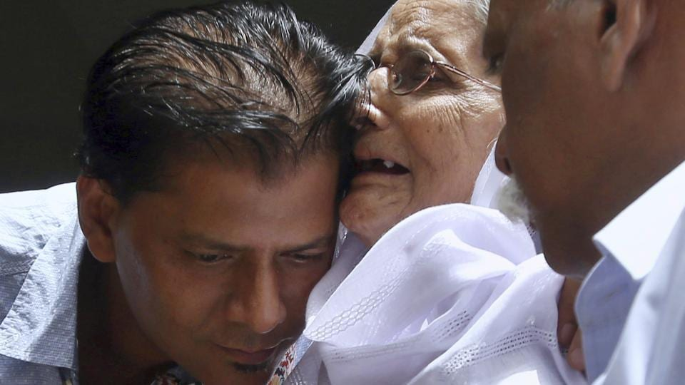 Abdul Aziz Sheikh (L), father of Sabika Sheikh, a victim of a shooting at a Texas high school, comforts an elderly woman at a condolence ceremony for his daughter at his home in Karachi, Pakistan. (Fareed Khan / AP)