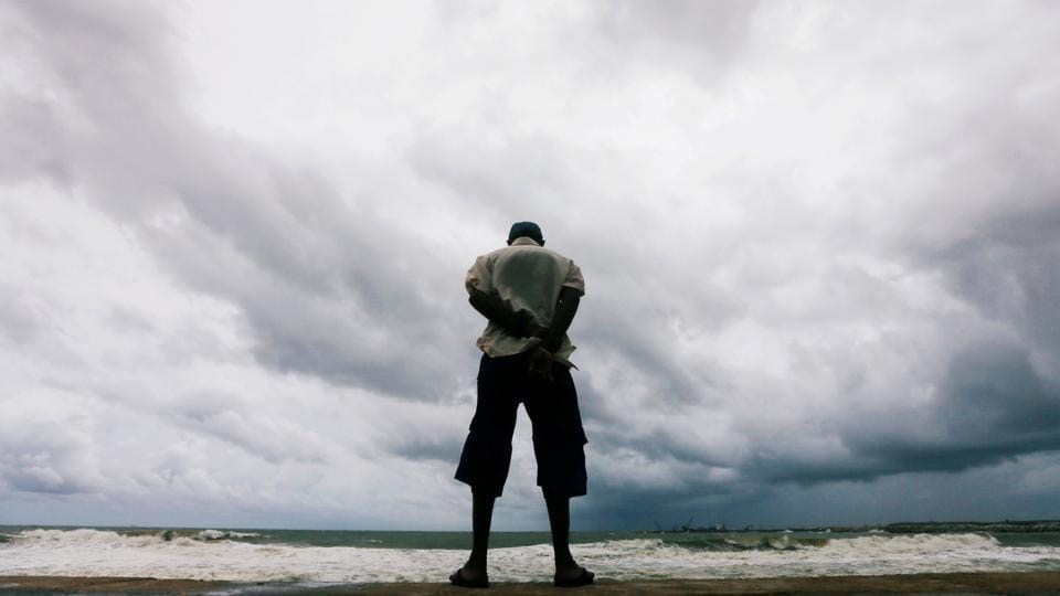 A man looks at the rough sea as rainy clouds gather above during the monsoon period in Colombo, Sri Lanka. (Dinuka Liyanawatte / REUTERS)