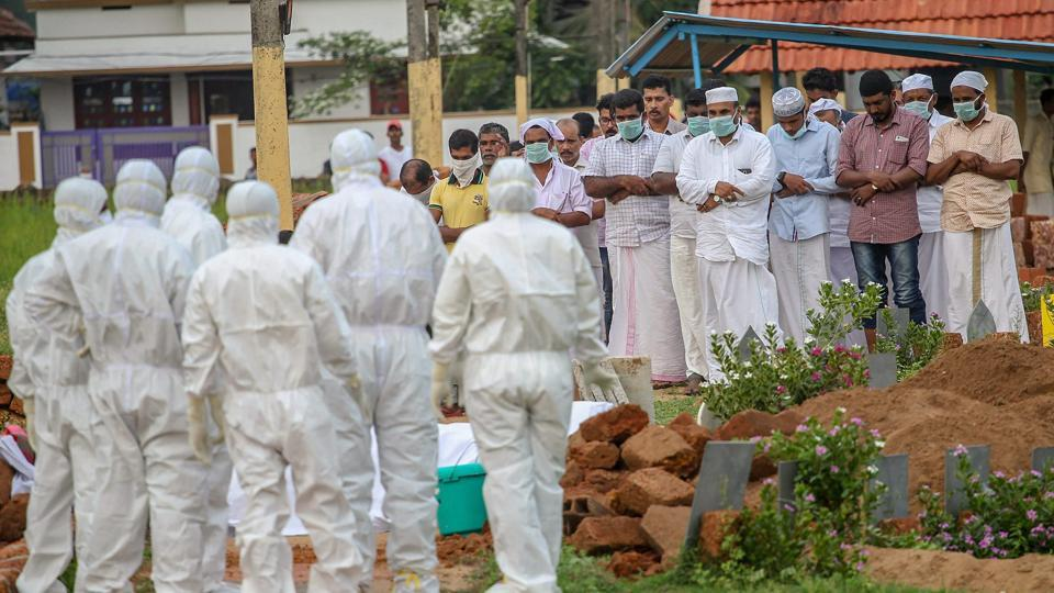 Relatives and hospital officals wear safety masks as they perform the last rites of a Nipah virus victim at a graveyrad in Kozhikode.