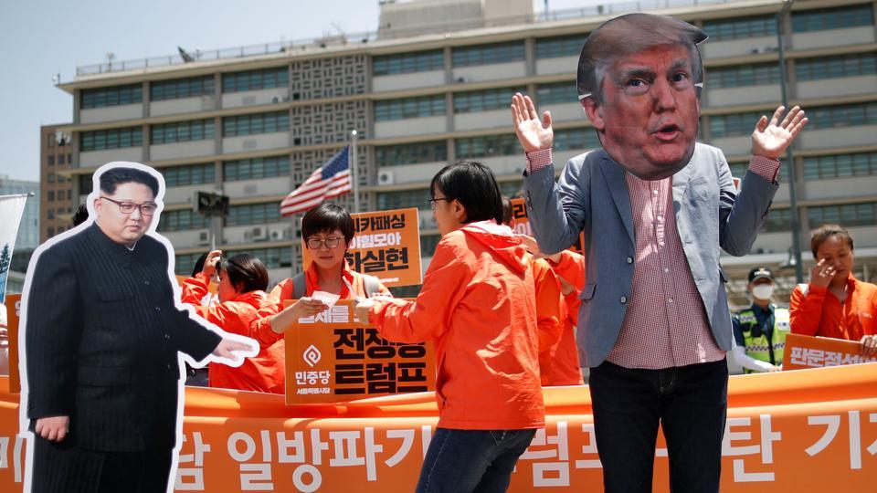 A man wearing a mask of US President Donald Trump performs next to a cutout of North Korean leader Kim Jong Un during an anti-US President Donald Trump rally near US embassy in Seoul South Korea