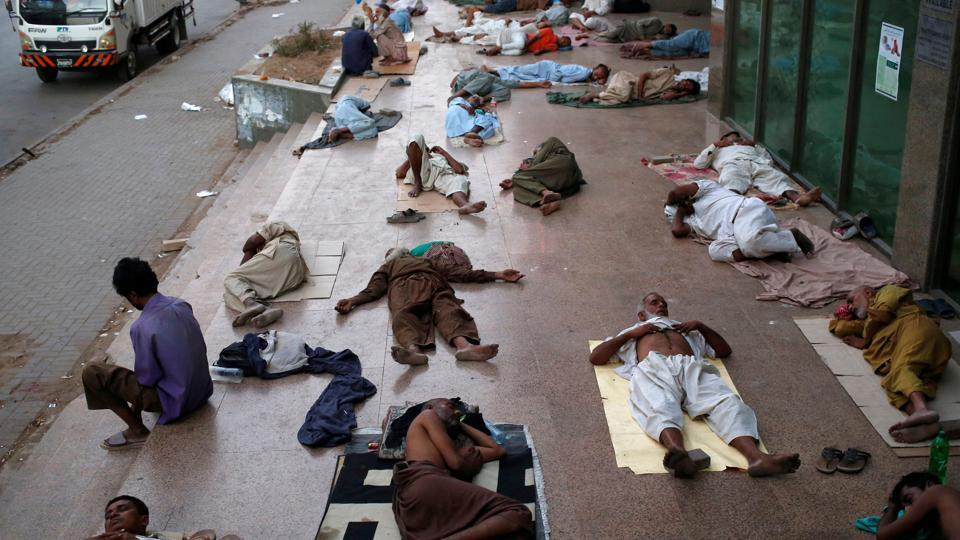 Residents sleep on a building pavement, to escape heat and frequent power outage in their residence area in Karachi, Pakistan. (Akhtar Soomro / REUTERS)