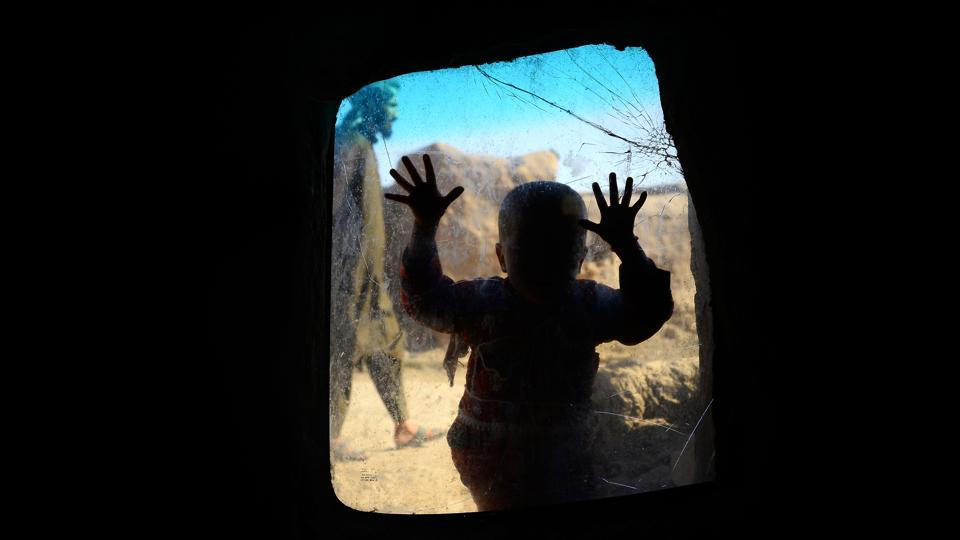 An internally displaced Afghan child looks on from a window in her temporary home at a refugee camp on the outskirts of Herat. (Hoshang Hashimi / AFP)