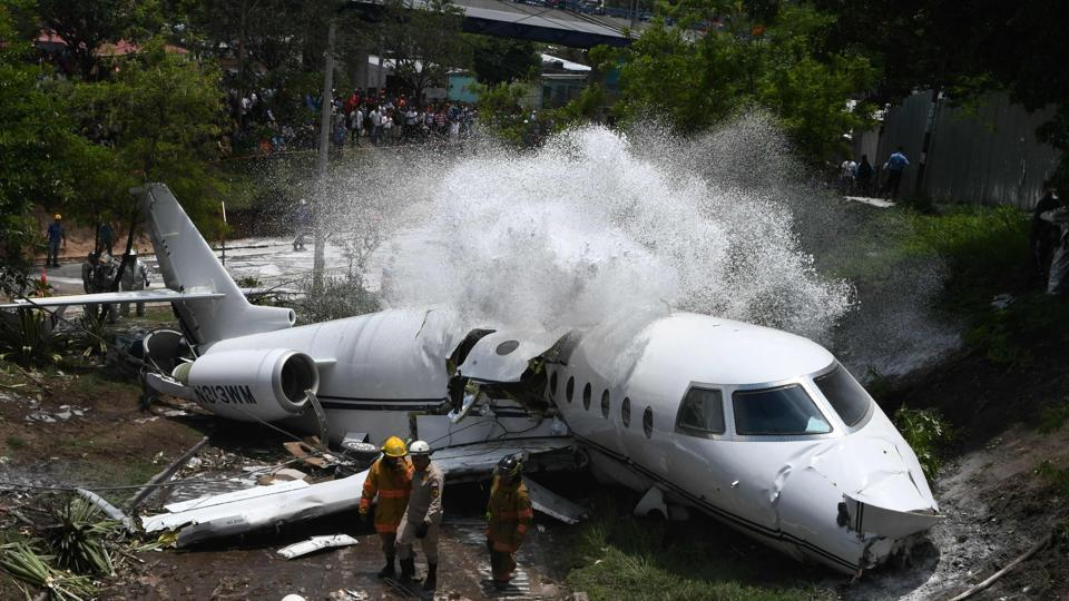 Firefighters spray foam on the wreckage of a plane, after it went off the runway at Toncontin International airport and collapsed over a busy boulevard in Tegucigalpa, Honduras. (Orlando Sierra / AFP)