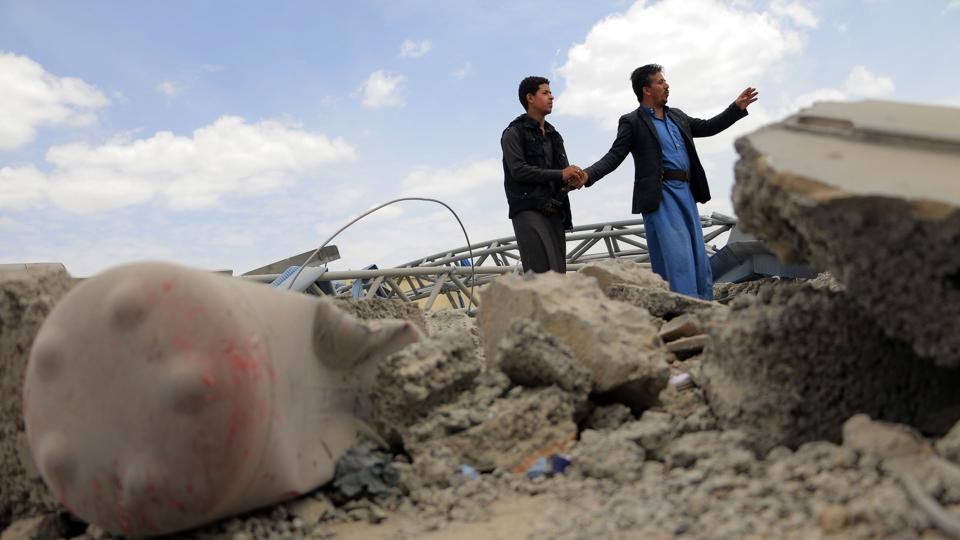 Men inspect a damaged petrol station after it was hit by alleged Saudi-led airstrikes on the outskirts the Yemeni capital Sanaa on May 21, 2018. (AFP)