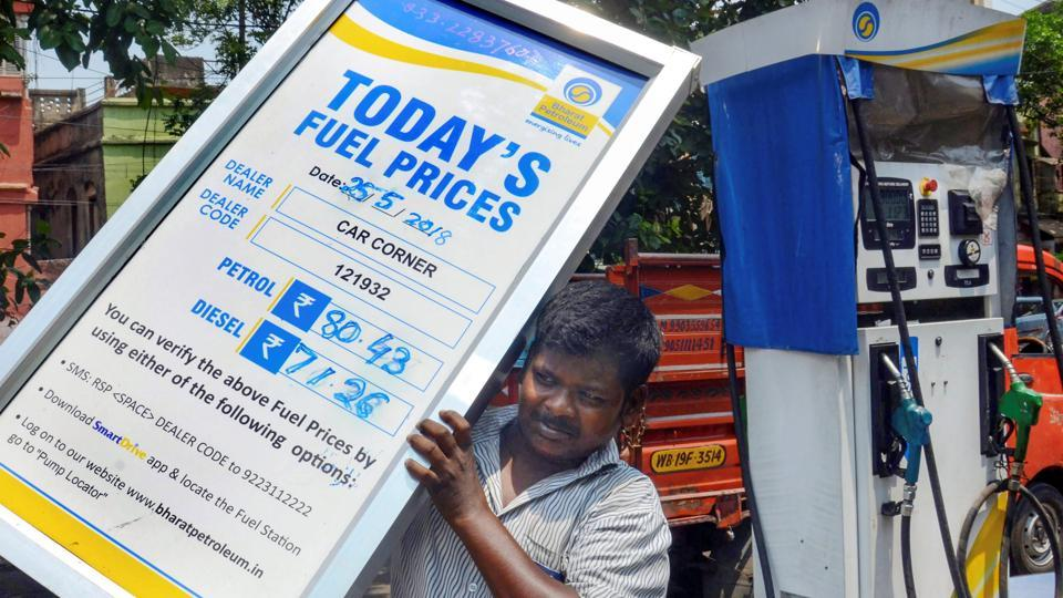 A petrol pump employee adjusts the price board at a fuel station as fuel prices record the highest-ever, in Kolkata, on Friday.