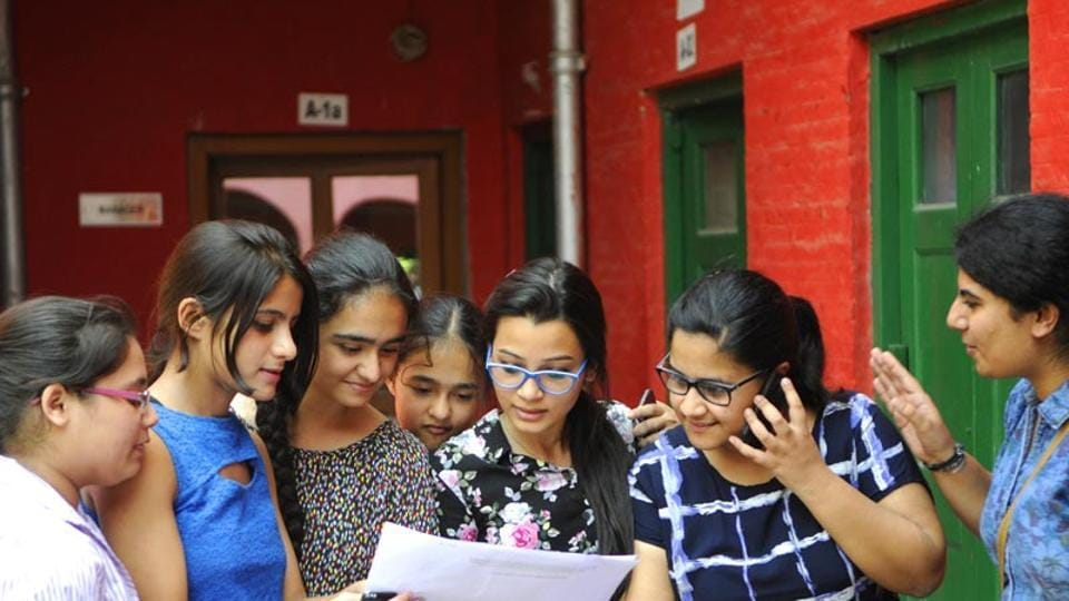 Students check CBSE exam results for Class 12 on Saturday, in New Delhi.