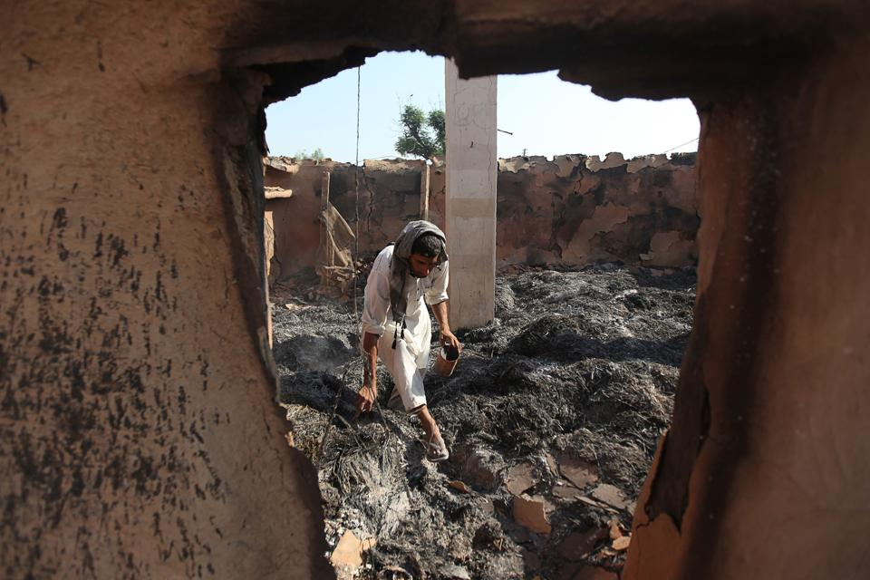 A villager inspects his damaged house following cross-border firing along India-Pakistan border, in Jammu.