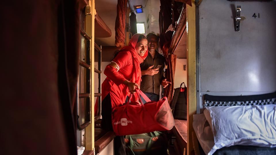 "Manju Devi hauls a passenger's luggage inside a train compartment. ""I weighed 30 kgs and the passengers' luggage was also 30 kgs but it was nowhere to the burden of feeding three children,"" Devi narrated earlier this year at the felicitation ceremony, with President Ram Nath Kovind in attendance. (Arun Sharma / PTI)"