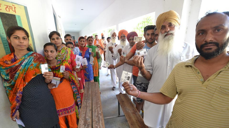 Voters with their ID cards outside a polling booth during in Lohian on Monday. (Pardeep Pandit/HT )