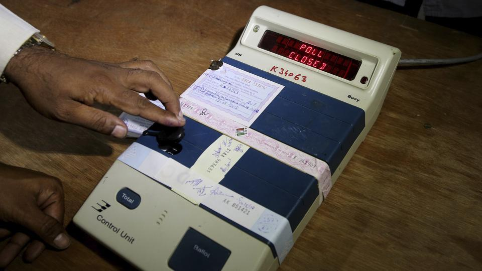 An election officer closes an electronic voting machine at the end of polls at a polling station in Bangalore on May 12, 2018.