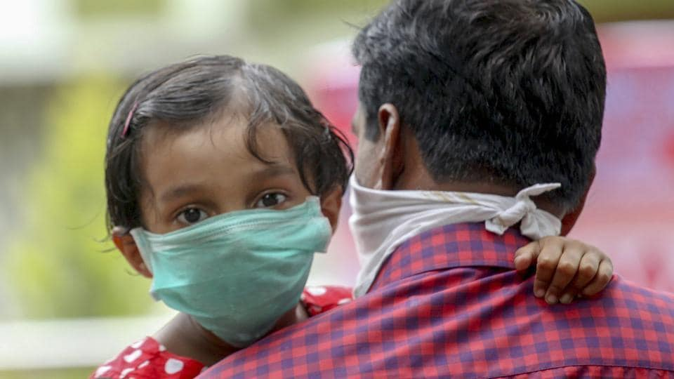 A child wears a safety mask as a precautionary measure after the 'Nipah' virus outbreak, at Kozhikode Medical College, in Kerala.