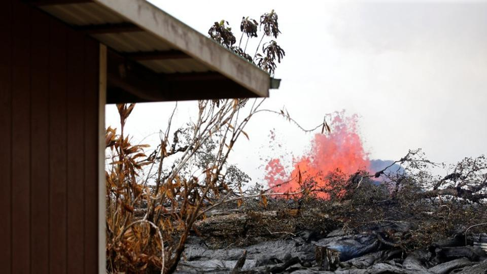 As a volcanic fissure spurts molten rock into the air, lava slowly approaches a home on Nohea Street in the Leilani Estates near Pahoa, Hawaii, on May 27, 2018.