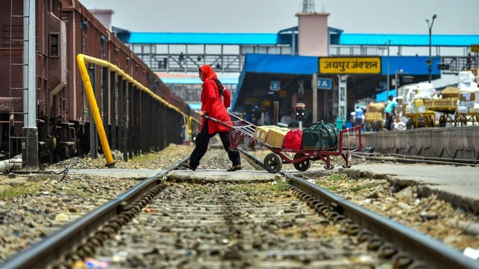 Manju Devi ferries luggage across the tracks at the Jaipur station. A porter's job is a physically demanding one, but with her children to take care of, Manju Devi takes on everyday with grit and determination. (Arun Sharma / PTI)