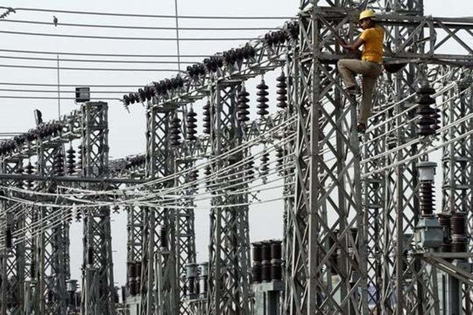 An employee works on electric pylons at a power station in Greater Noida on the outskirts of New Delhi June 8, 2012.