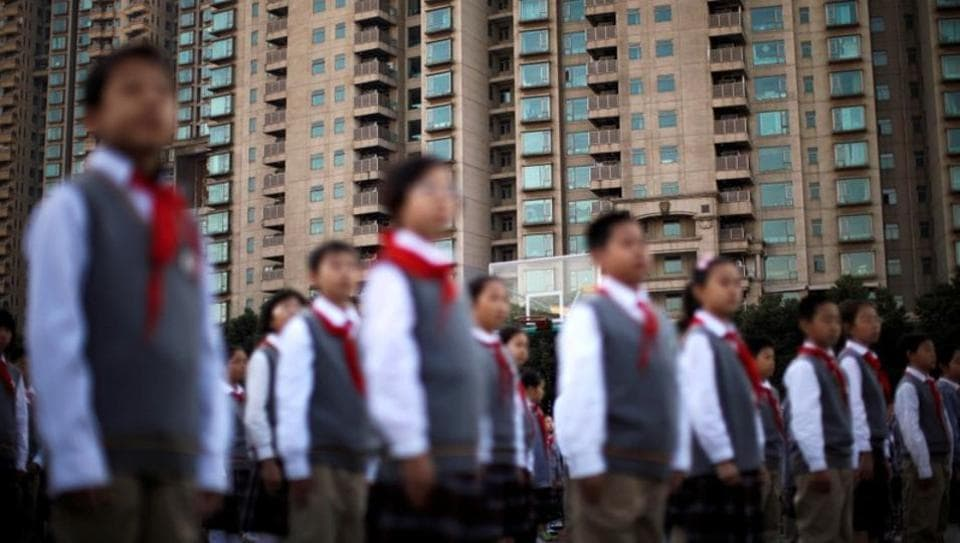 Members of Young Pioneers of China gather at the weekly flag-raising ceremony at a school in Shanghai, China.