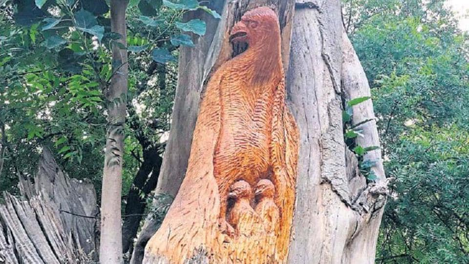 A carved bird, along with her babies, is one of the renderings on a dead tree of Delhi's Lodhi Garden.