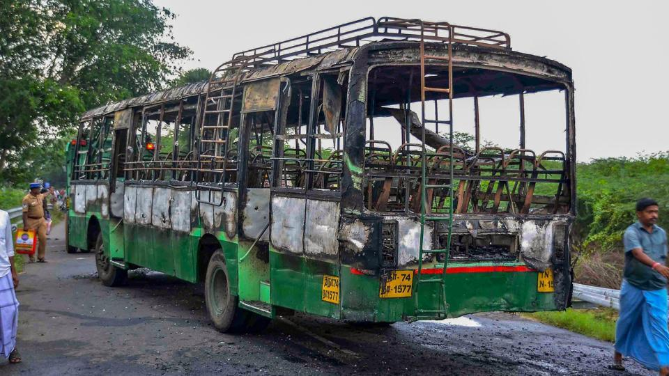 A man walks past a vandalised government bus during a violent protest against the closure of Vedanta's Sterlite Copper unit, in Thootukudi.